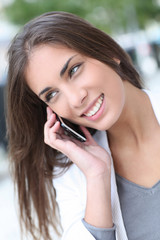 Smiling beautiful girl talking on telephone in town