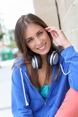 Beautiful teenager sitting outside with headphones