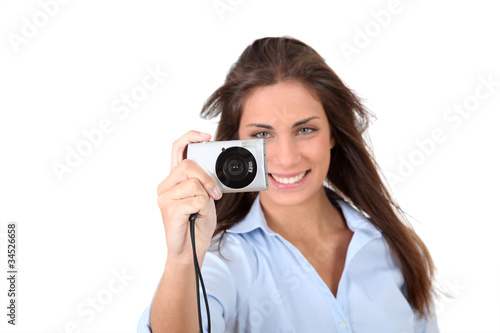 Portrait of beautiful woman using compact digital camera