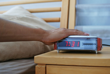 Hand Trying to Push the Snooze Button on Alarm Clock