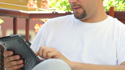 Young man with tablet computer, outdoors