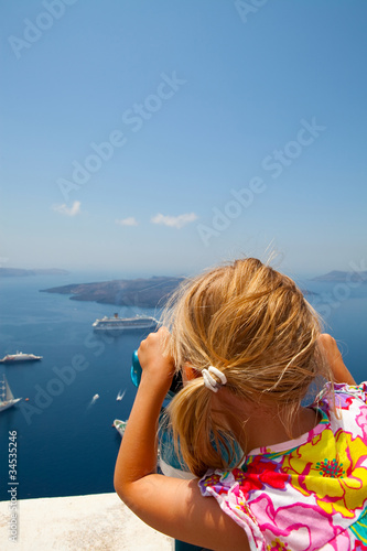Girl looking with binoculars in Thira, Santorini, Greece
