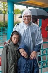 Famille en imperméable sous la pluie