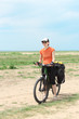 bicycle tourist girl standing on road, blue sky and horizon