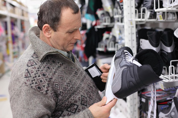elderly man in gray sweater chooses skates in big sports shop