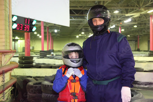 little boy and his carting trainer are standing in helmets