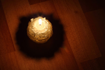 round yellow candle with glitter on brown floor; light from flam
