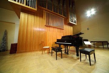 Massive wooden pipe organ and black concert grand piano