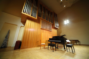 Massive wooden high pipe organ and black concert grand piano