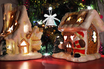 two decorative Christmas toy houses, bell on Christmas tre