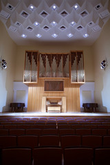 Wooden pipe organ with control panel in empty concert hall