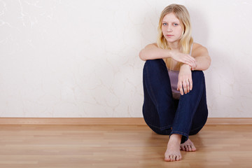 Young girl sits on floor with her back pressed against wall