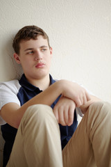 Teenager sits leaning back against wall