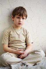 Little boy sits alone on a fleecy white rug