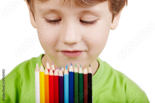 portrait of little boy in green t-shirt who examine pencil