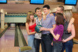 Fellow holds ball for bowling and friends stand alongside
