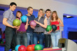 Friends stand near stand ruling balls and hold balls for bowling