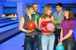 Постер, плакат: Five friends stand with balls for bowling and look on each other