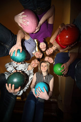 Girls and youths stand in close circle with balls for bowling