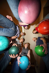 Friends stand in circle and everybody hold ball for bowling