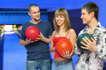 Two men holds balls for bowling and look at girl in center