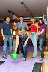 Girl prepares for throw ball in bowling and friends hearten it