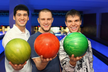 Friends stand alongside and in hands hold balls for bowling