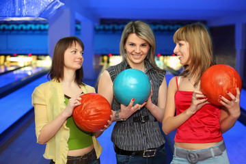 Three girlfriends hold balls for bowling and look on each other