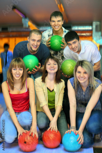 Girls of squatting and fellows  back stand with ball for bowling