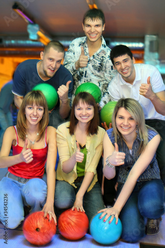 girls of squatting and three men behind with balls for bowling
