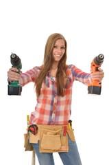 Junge Handwerkerin mit zwei Bohrschraubern
