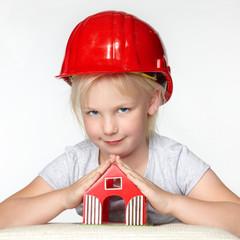 Little girl with building-site helmet protecting a wendy house