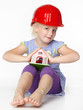 Cute girl with building-site helmet protecting a wendy house