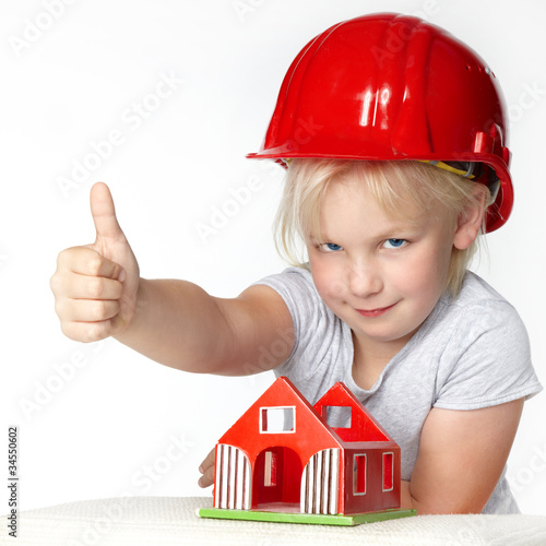 Little girl with helmet showing thump up for building a house
