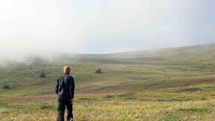 The man goes afar on a grass in fog strips
