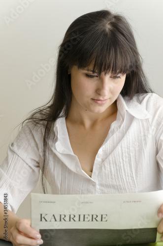 Junge Frau liest Karrierezeitung