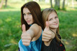 "two young women showing ""thumbs-up sign"""