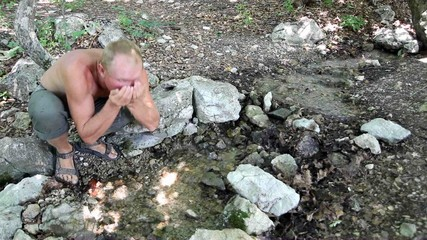 man drinks from palms water from a stream