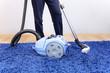 Vacuum cleaner in action-men cleaner a carpet.