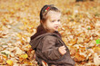 Adorable baby girl plays in autumn forest in a pile of leaves