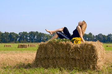Girl in the field Girl is sitting on sheaf hay at the field