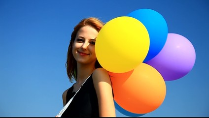 Redhead girl with colour balloons at blue sky background.