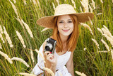 Redhead girl with old camera at outdoor.