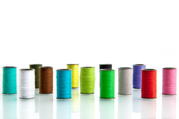 Pile of coloured bobbins of lurex thread