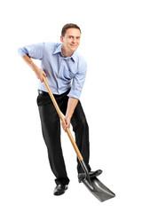 Full length portrait of a businessman  holding a shovel