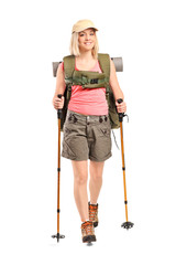 Portrait of a smiling woman with backpack and hiking poles