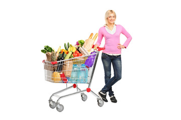 Portrait of a young woman posing next to a shopping cart