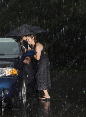 Leinwanddruck Bild Woman locked out of her car in the rain