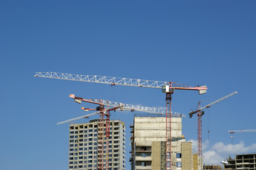 Building crane at the background of a multi-storey building