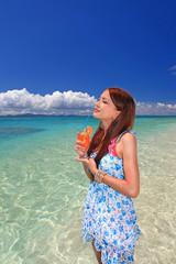 日光浴をしながらトロピカルジュースを飲む女性
